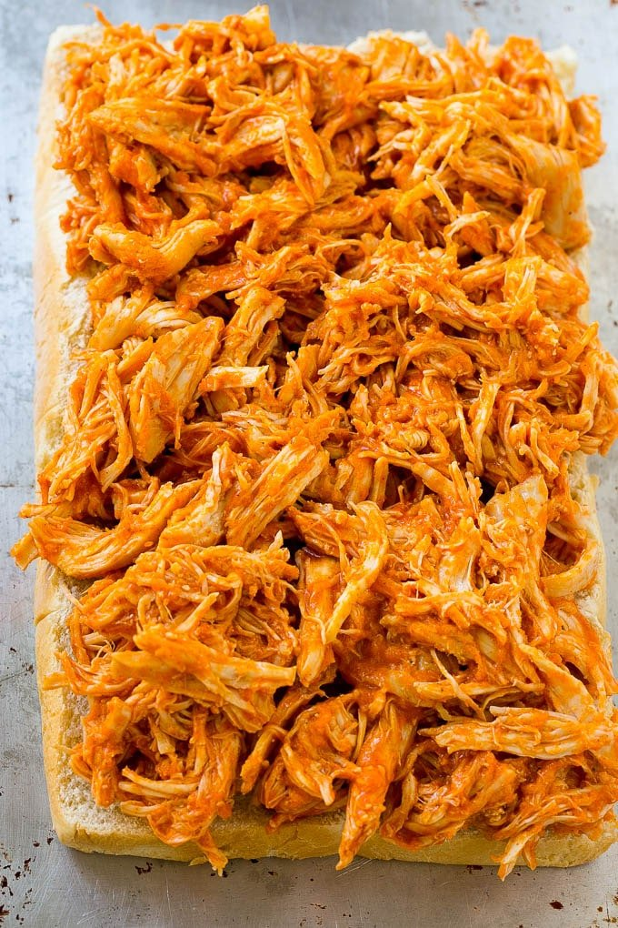 Shredded buffalo chicken spread over slider buns.