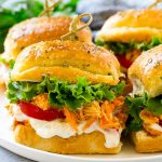 A plate of buffalo chicken sliders layered with lettuce, tomato and ranch.