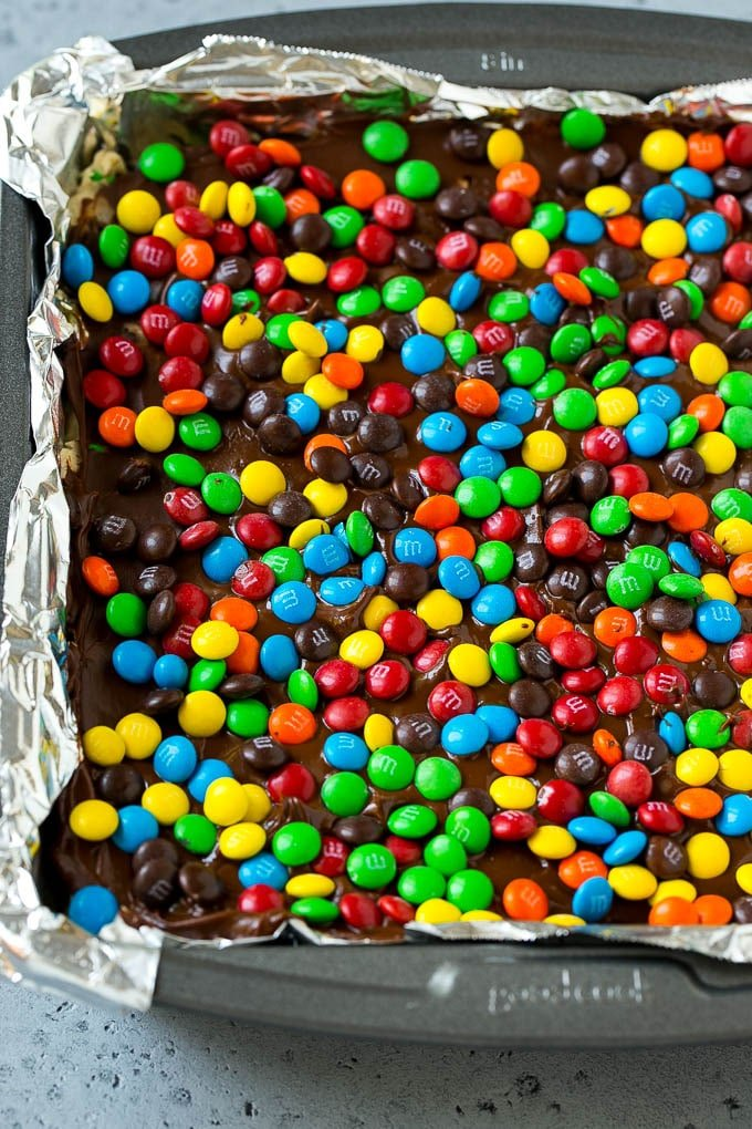 A pan of cookie dough bars topped with chocolate and miniature M&M's.