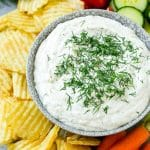 A bowl of creamy dill dip served with potato chips and vegetables.