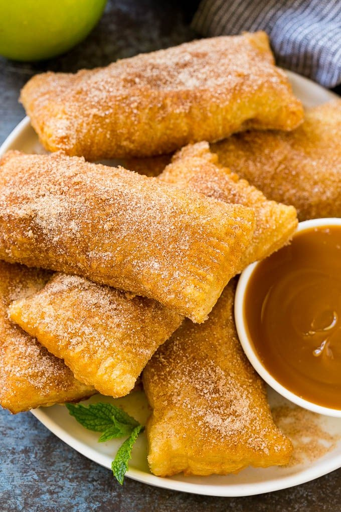 A plate of deep fried apple pies dusted with cinnamon sugar.