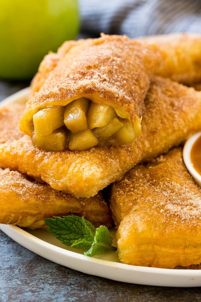 Fried apple pies on a plate served with caramel sauce and topped with cinnamon sugar.