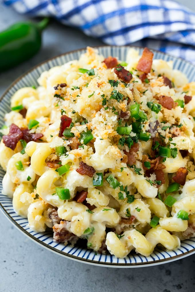 A bowl of jalapeno popper mac and cheese topped with crispy breadcrumbs, bacon and jalapeno peppers.
