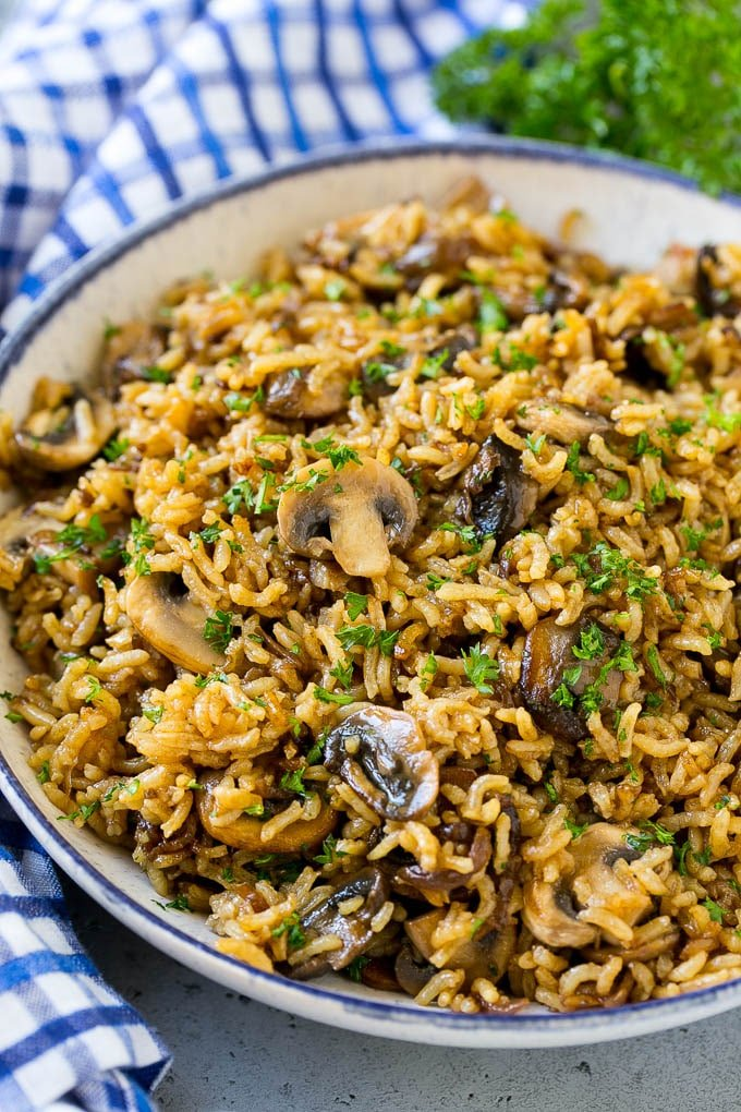 A bowl of baked mushroom rice topped with chopped parsley.