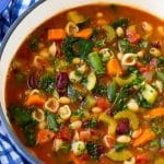 A pot of Olive Garden minestrone soup loaded with vegetables, beans and pasta.