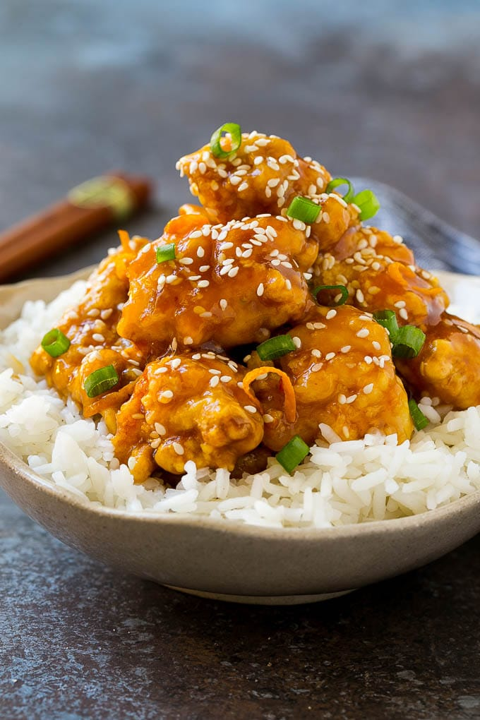 A bowl of orange chicken served over steamed rice and topped with sesame seeds.