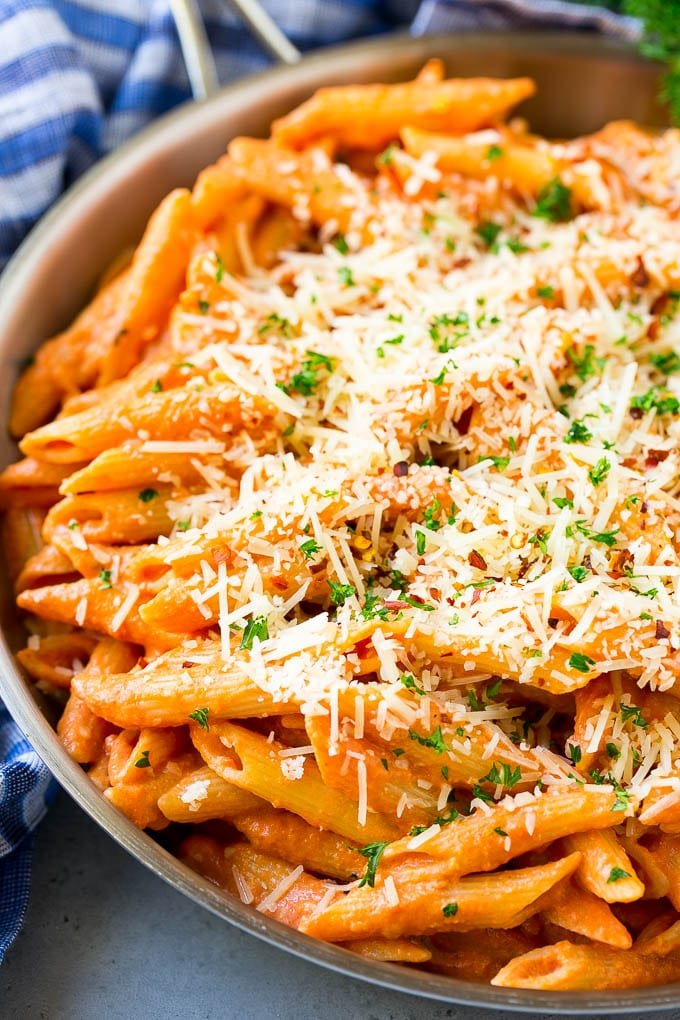 A skillet of penne alla vodka topped with shredded parmesan cheese.