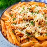 A bowl of penne alla vodka pasta topped with parmesan cheese, parsley and red pepper flakes.