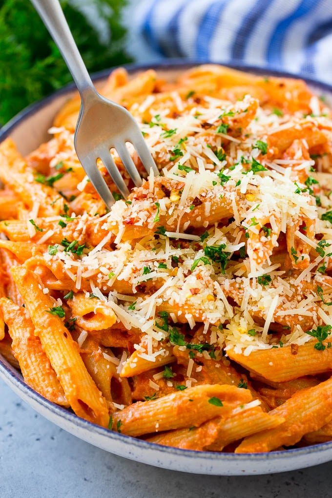 A bowl of penne alla vodka with a fork in it.