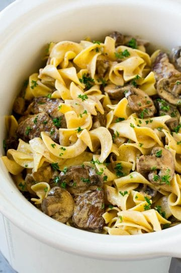 Slow cooker beef stroganoff with chunks of beef, mushrooms and egg noodles topped with parsley.