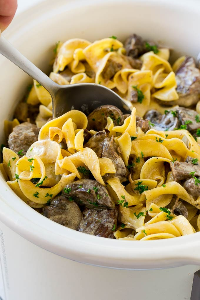 A crock pot of beef stroganoff with a serving spoon in it.