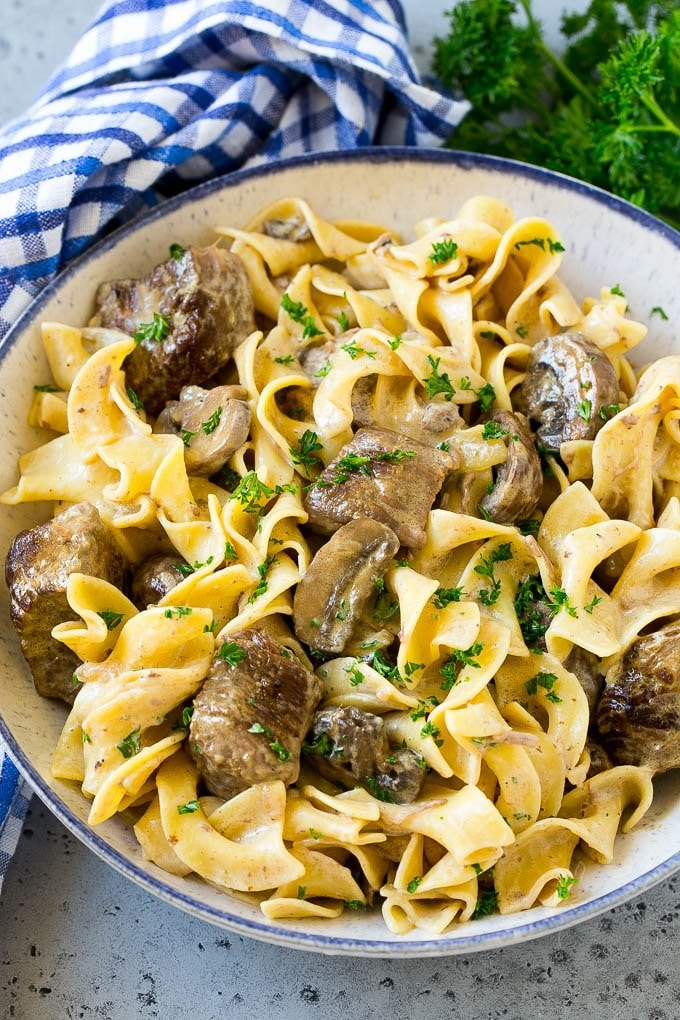 A bowl of slow cooker beef stroganoff with egg noodles.