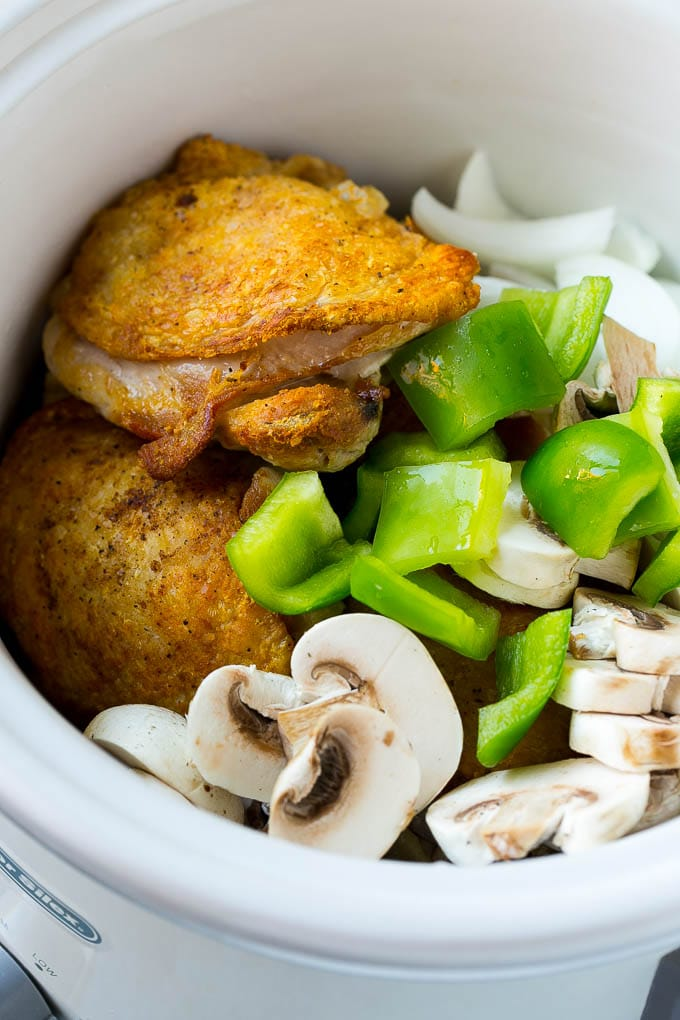Chicken thighs in a slow cooker with onions, peppers and mushrooms.