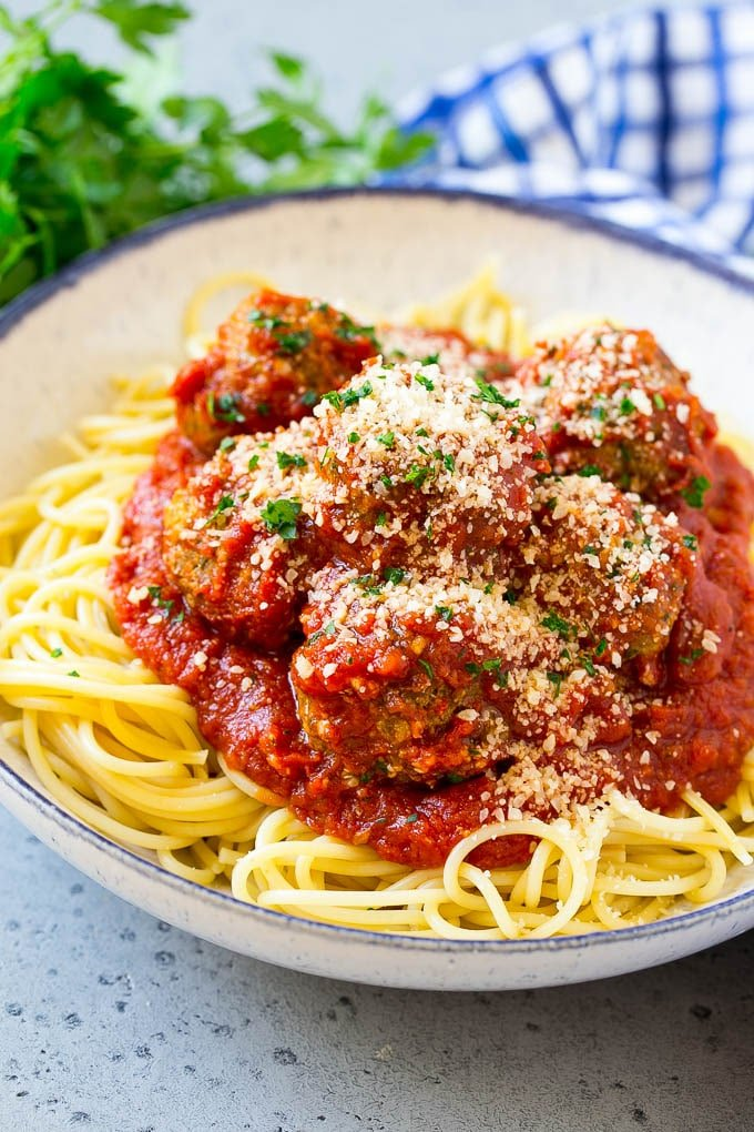 Slow cooker meatballs served over spaghetti, topped with parsley and parmesan cheese.