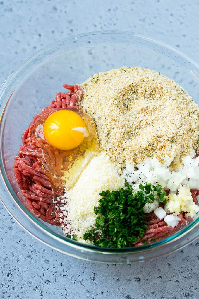 Ground beef, onion, garlic, herbs, cheese and breadcrumbs in a mixing bowl.