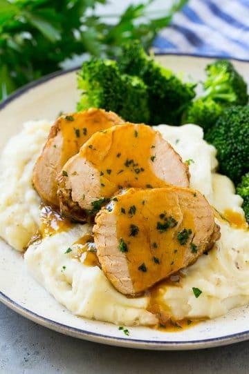 Sliced slow cooker pork tenderloin served over mashed potatoes with broccoli.