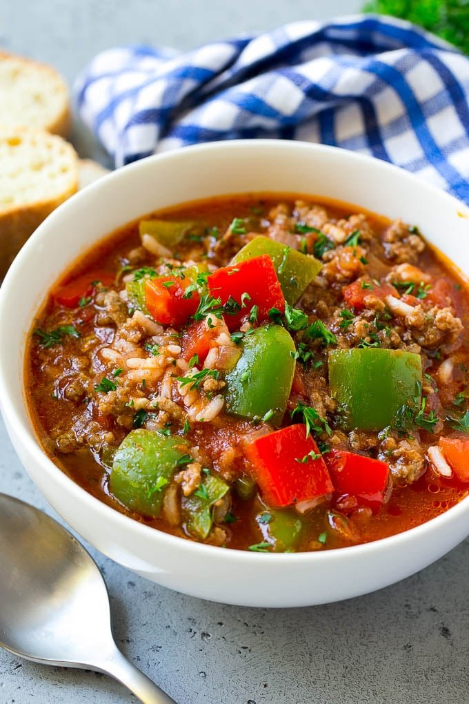 A bowl of stuffed pepper soup with ground beef, peppers and rice.