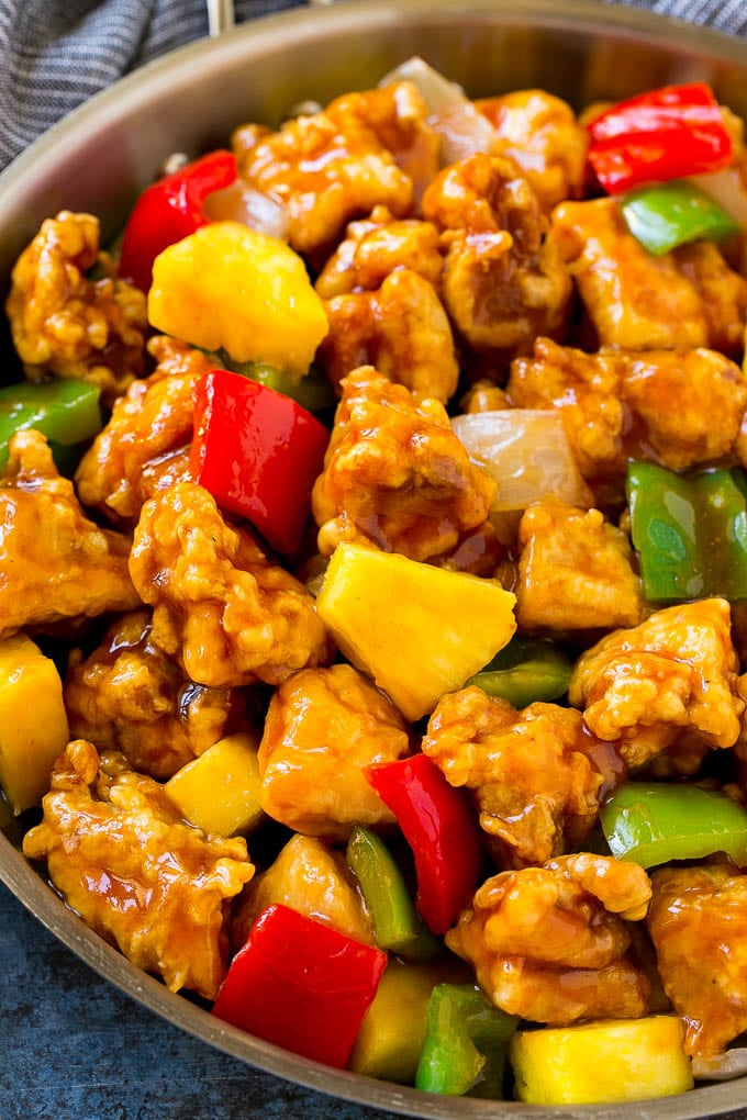 A frying pan of sweet and sour chicken with crispy chicken, pineapple, bell peppers and onions.