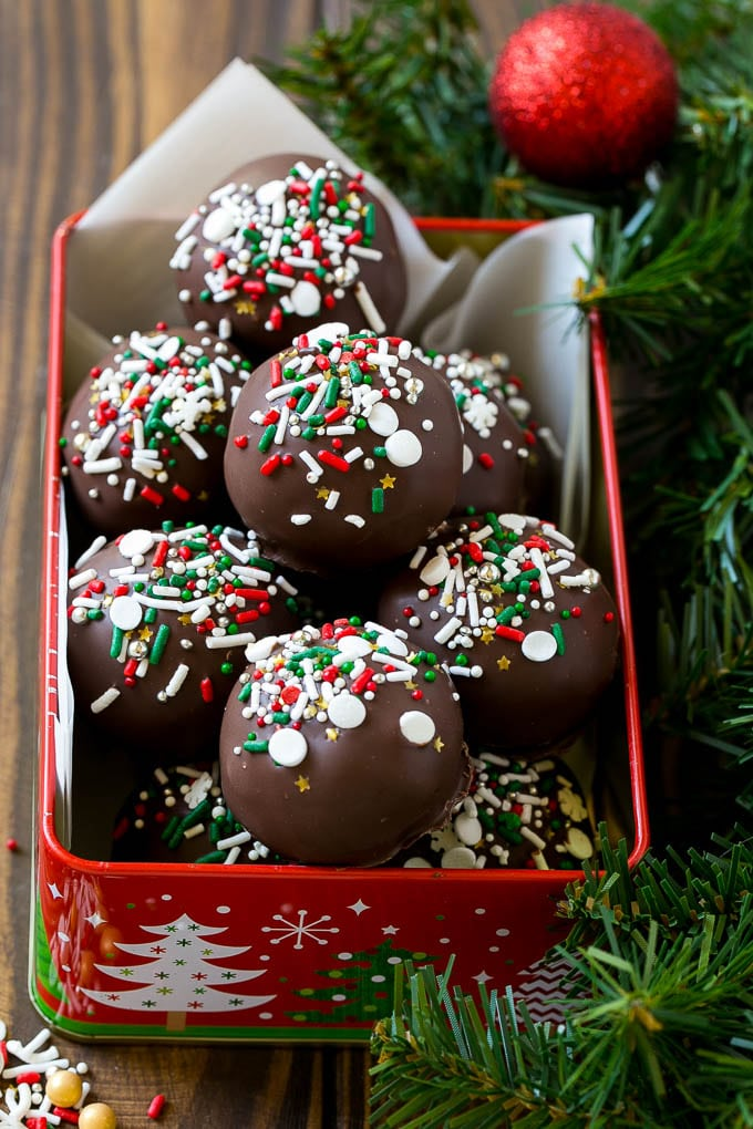 Cake truffles in a gift tin coated in dark chocolate and sprinkles.