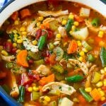 Chicken vegetable soup full of chicken, veggies and potatoes in tomato broth.