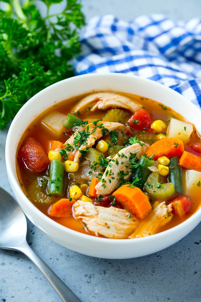 A bowl of chicken vegetable soup topped with parsley.