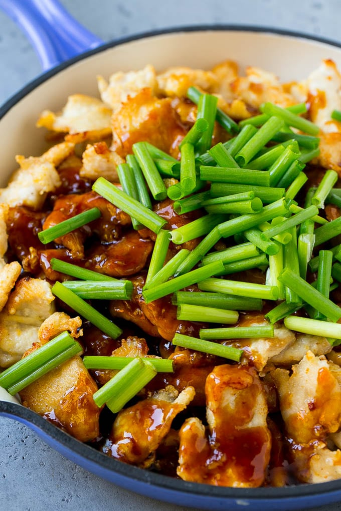Sliced chicken breast in a skillet with Mongolian sauce and green onions.