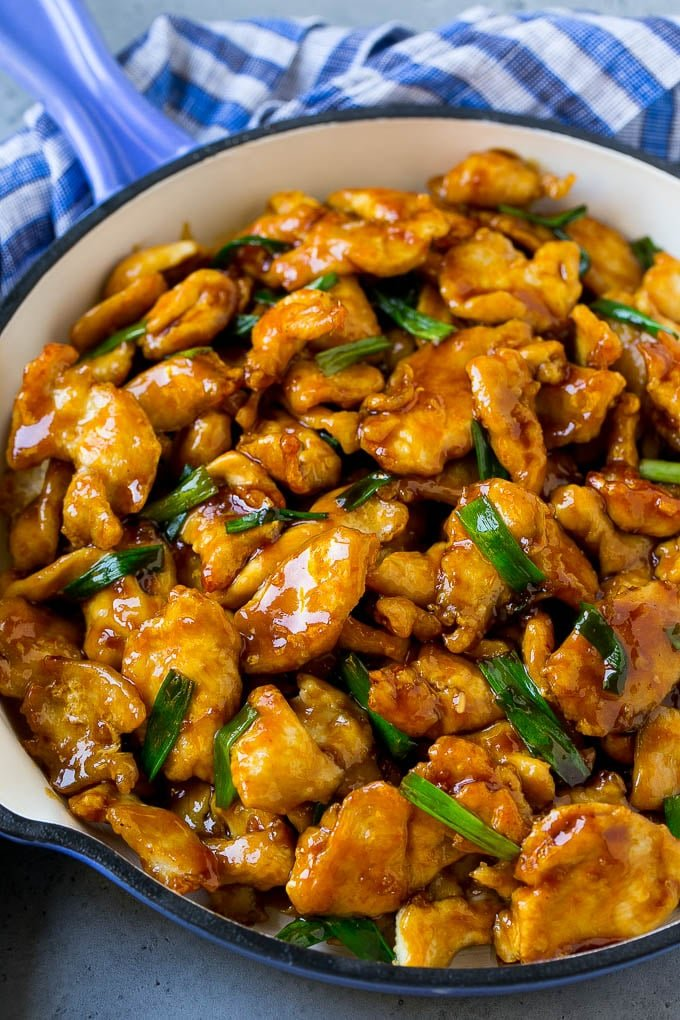 Mongolian chicken with green onions in a skillet.
