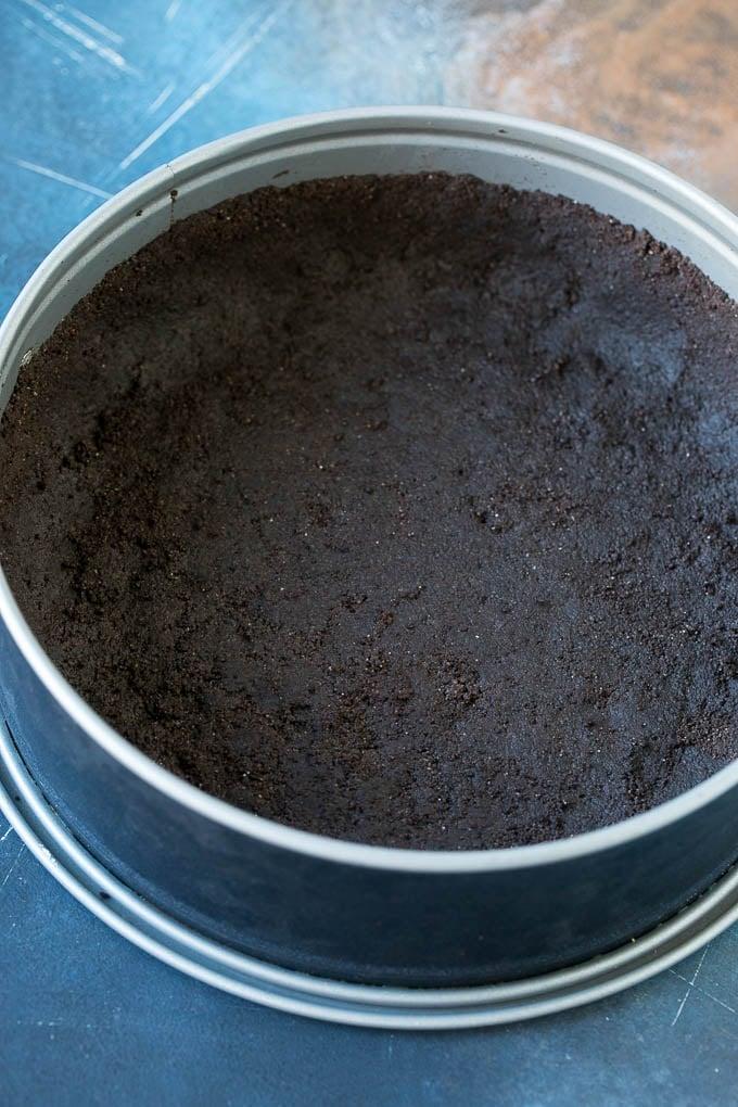 A no bake Oreo crust in a springform pan.