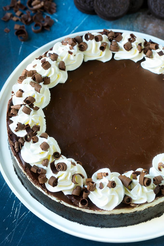 A no bake Oreo cheesecake topped with chocolate ganache, whipped cream and chocolate curls.