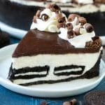 A slice of no bake Oreo cheesecake with a cookie crust, cheesecake and Oreo filling and chocolate topping.