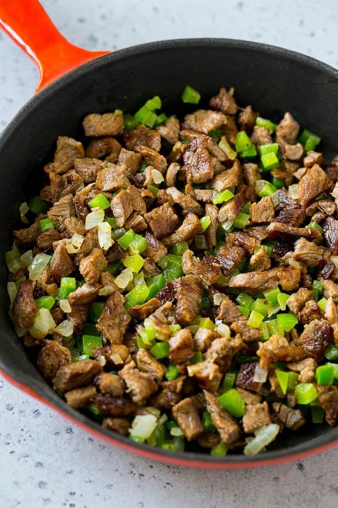 Seared rib eye steak, peppers and onions in a pan.