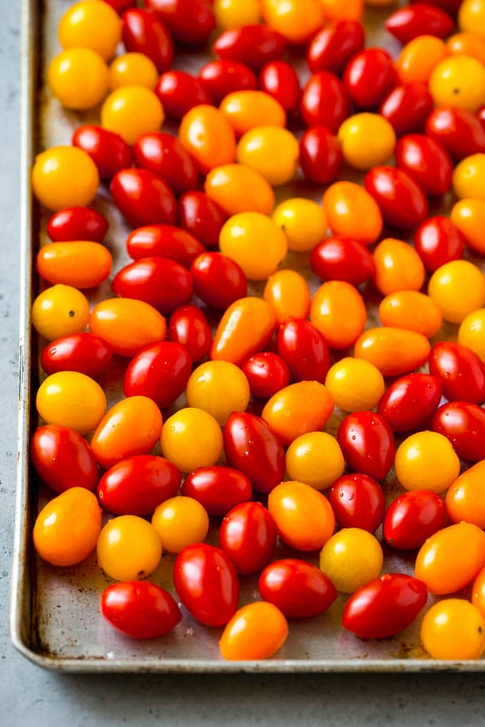 Red, orange and yellow cherry tomatoes on a sheet pan.