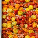 Roasted cherry tomatoes with garlic, olive oil and herbs on a sheet pan.