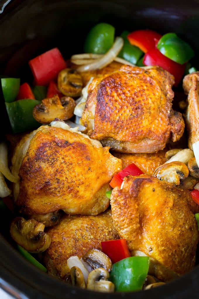 Chicken thighs with peppers, onions and mushrooms inside a slow cooker.