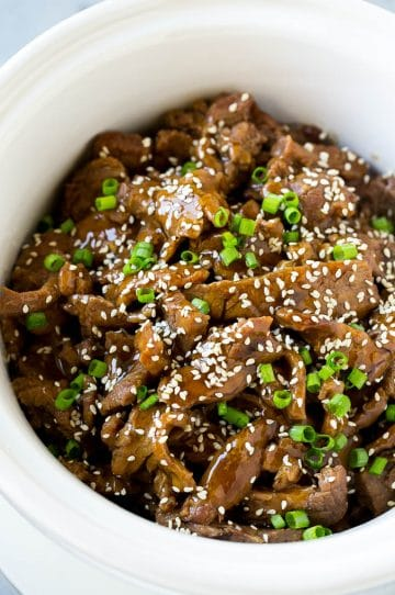 Slow cooker Korean beef with flank steak slices in a sweet and savory sauce, all inside a crock pot.