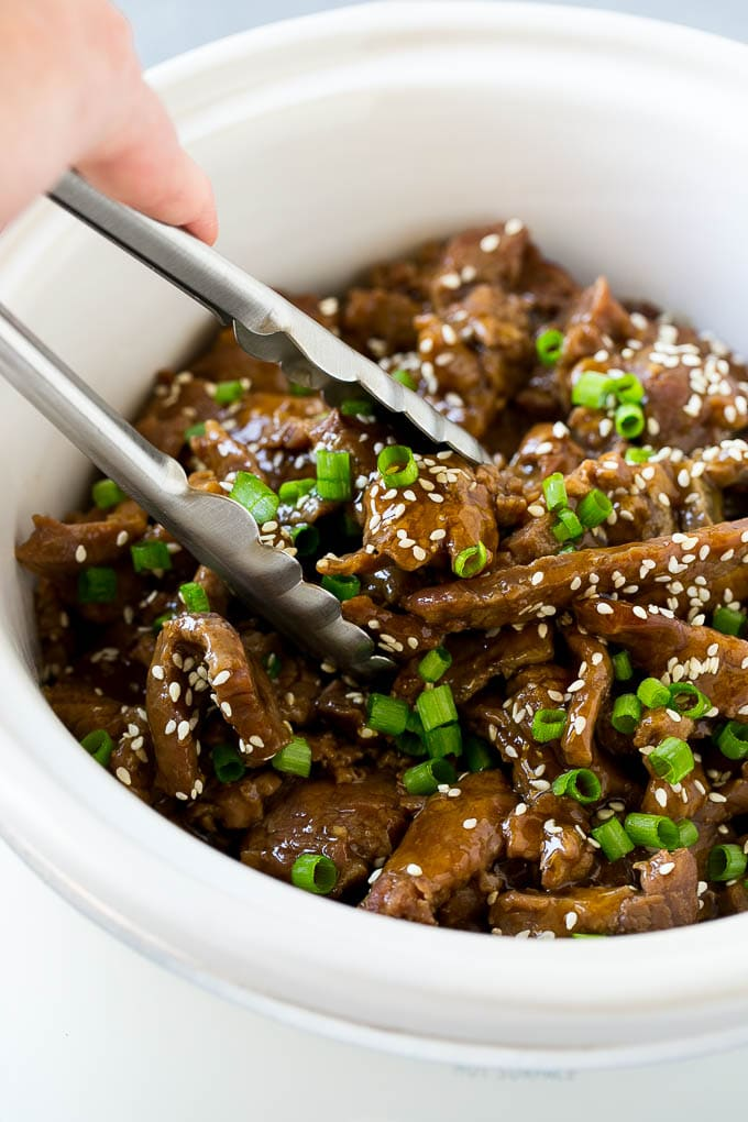 A crock pot of Korean beef with serving tongs in it.