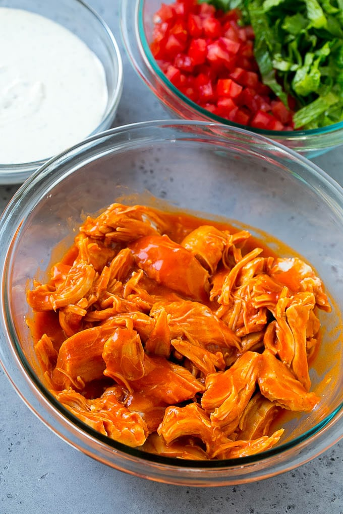 Chicken tossed with buffalo sauce along with bowls of ranch, tomatoes and lettuce.