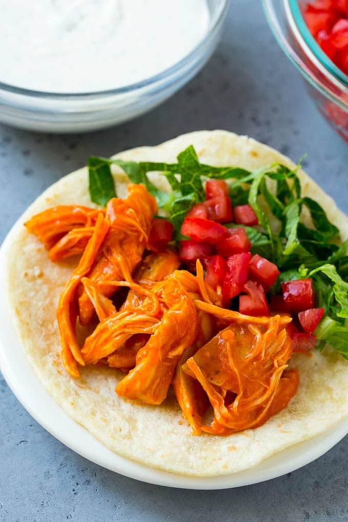 Buffalo chicken, tomatoes and shredded lettuce on a tortilla.