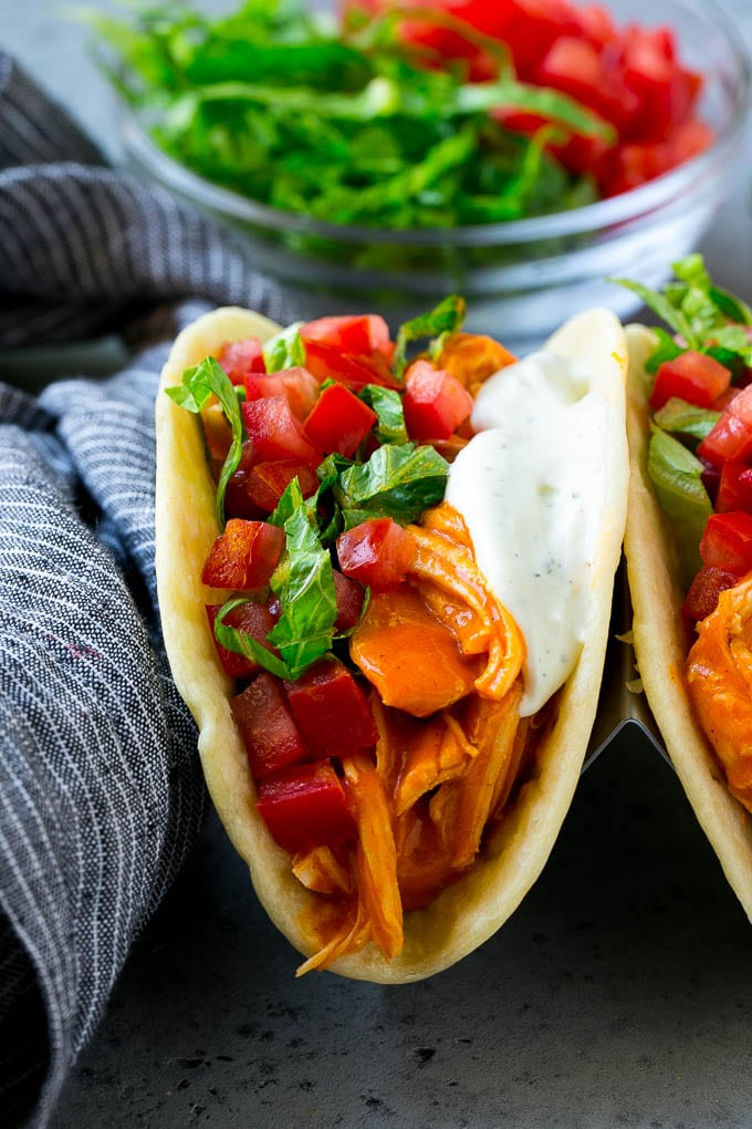 Buffalo chicken tacos with spicy chicken, diced tomato, shredded lettuce and ranch dressing.