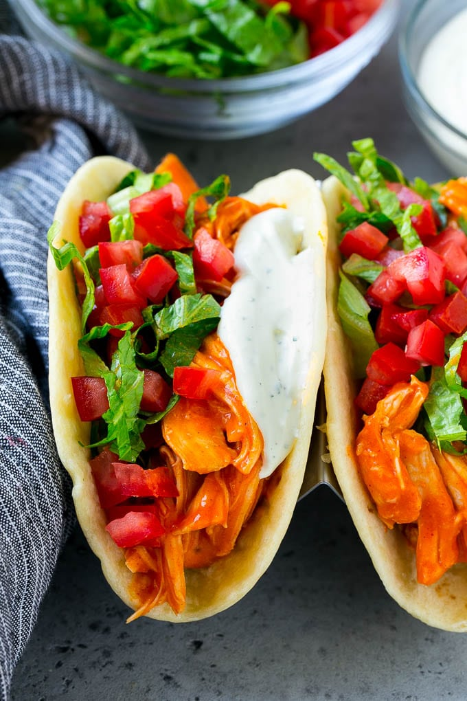 Buffalo chicken tacos filled with shredded chicken, lettuce, tomato and ranch sauce.