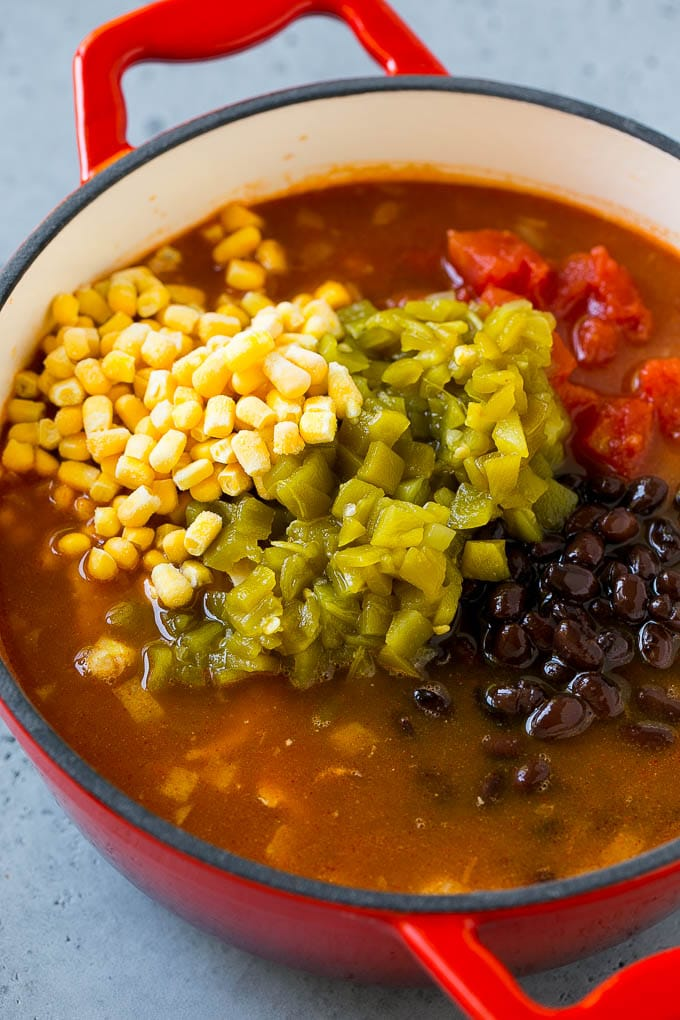 A soup pot full of shredded chicken, tomatoes, chiles, black beans, corn and broth.