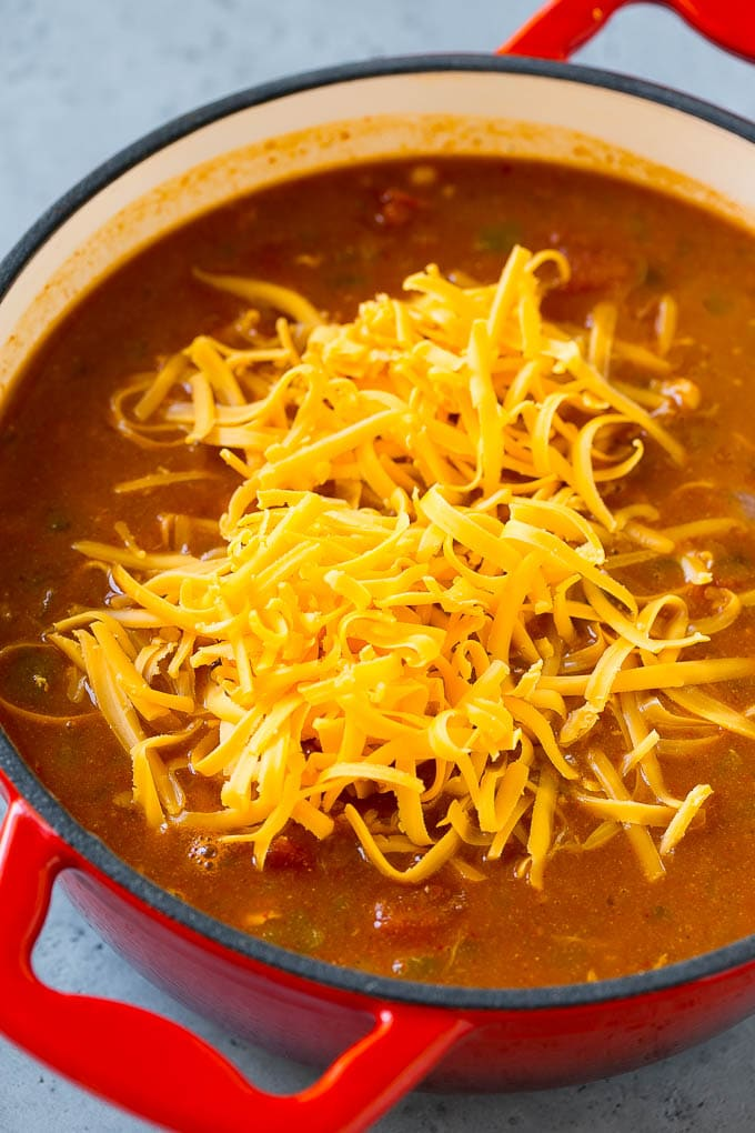 Chicken enchilada soup with cheddar cheese on top.