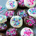 Chocolate covered Oreos decorated with pink and purple sprinkles.