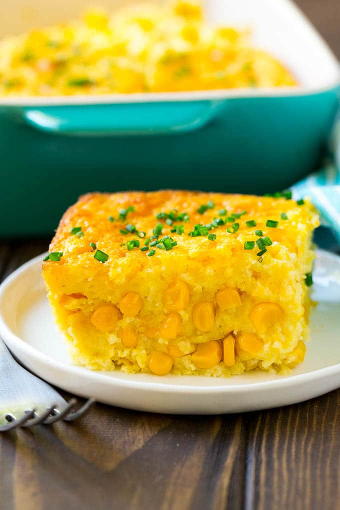 A serving of corn pudding on a plate, garnished with chives.