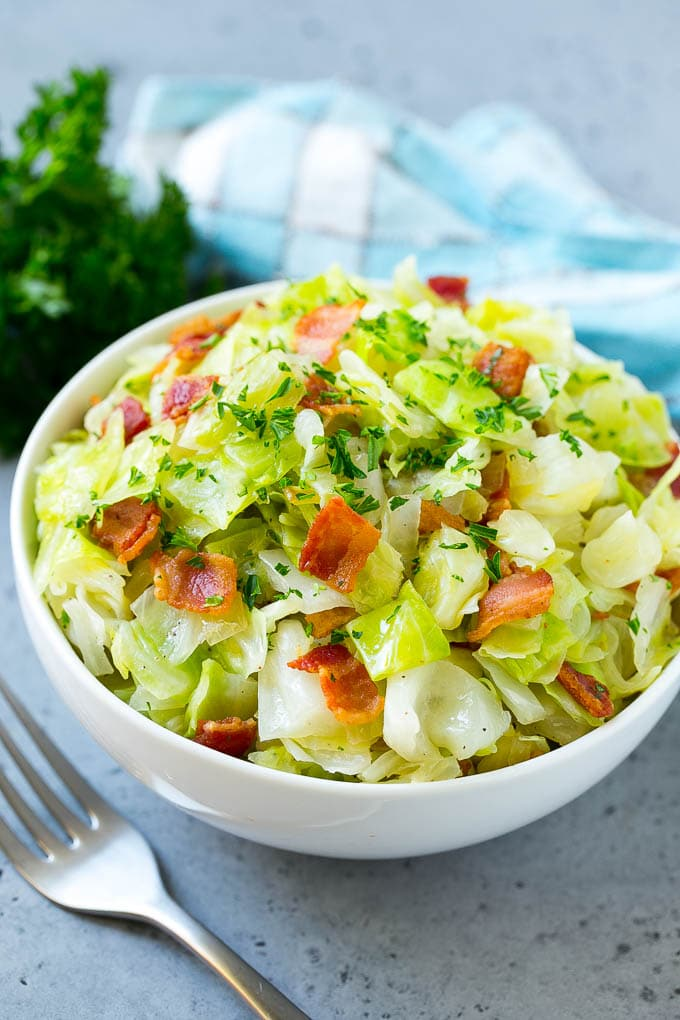 A bowl of fried cabbage topped with bacon and parsley.