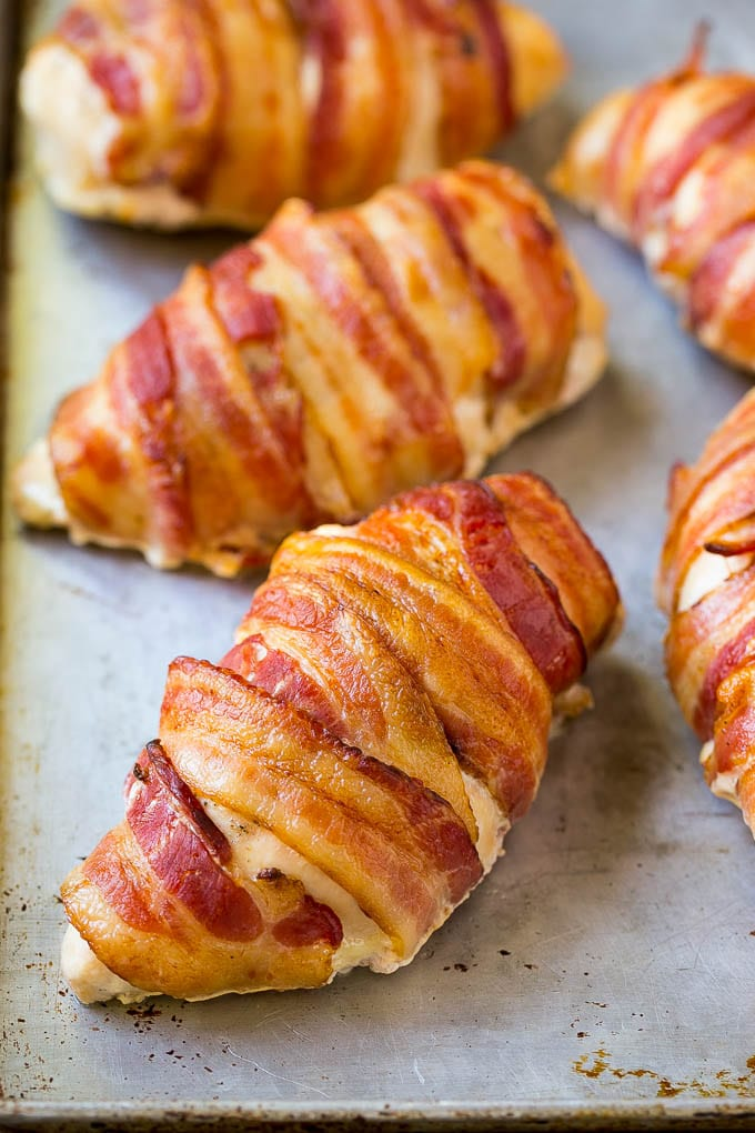 Bacon wrapped chicken breasts on a sheet pan.