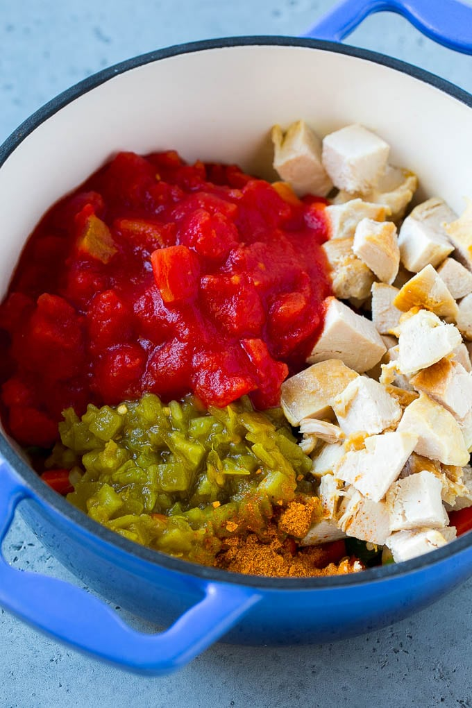 Vegetables, chicken, chiles and tomatoes in a pot.