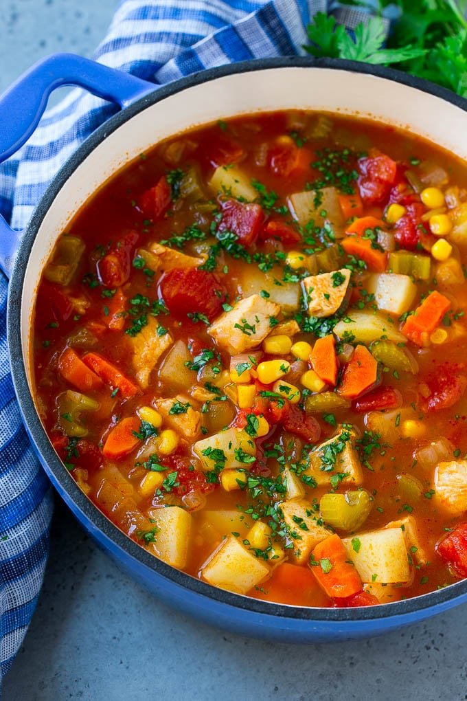 A pot of Mexican chicken soup with colorful veggies and potatoes, all topped with cilantro.