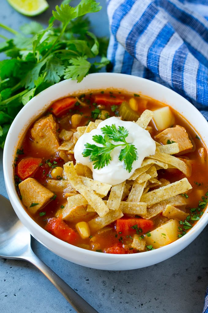 A bowl of Mexican chicken soup topped with tortilla strips and sour cream.