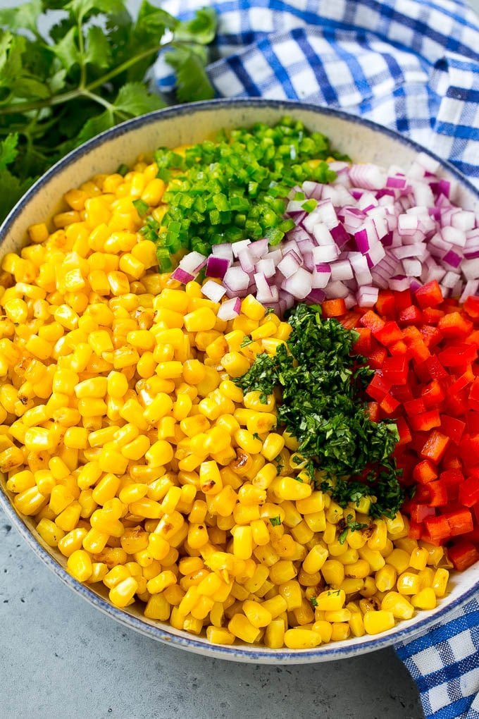 A salad bowl full of corn, red bell pepper, jalapeno, onion and cilantro.